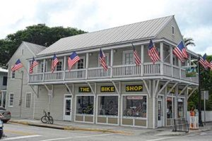 Exterior Shop photo. Gray painted building with white trim. and USA flag