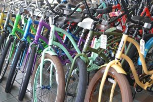 Misc. colored bikes lined up side by side, inside store