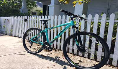 Aqua color bike, parked along a white picket fence.