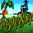 Small The Bike Shop Key West Header Logo. Colorful background of sky, ocean palm tree and grass. With a person riding a bike.